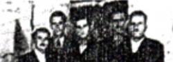 """Απρίλιος 1944. Τα μέλη της """"ομάδας"""" της Θεσσαλονίκης στέκονται πίσω από τον ασύρματο, στο Εβραϊκό υφαντουργείο. Από αριστερά: ο Νίκος Ωραιόπουλος, ο Κοσμάς Γιαπιτζόγλου, ο Ηλίας Δουνδουλάκης, και οι φύλακες, ο Νικήτας, και ο Σταύρος."""