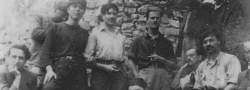 "1942. The Psiloritis Mountains hideout with Manolis Bandouvas, center foreground with cigarette. George Doundoulakis, far left. Patrick Leigh Fermor with cigarette standing behind Bandouvas. John Androulakis, standing next to George with black ""mandili"" or headscarf. Bandouvas' bodyguards on right."