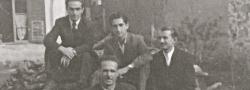 Juni, 1944. Im Hof der Textil Fabrik in Saloniki. Sitzend auf dem Holzstapel von links, oberste Reihe: Odysseus (Yiapitzoglou's Kusin), Helias Doundoulakis und Nicos Oreopoulos; im Vordergrund, Nikitas. Im Hintergrund ist Kyria Eleni's Wohnung mit Fensterläden zu sehen.